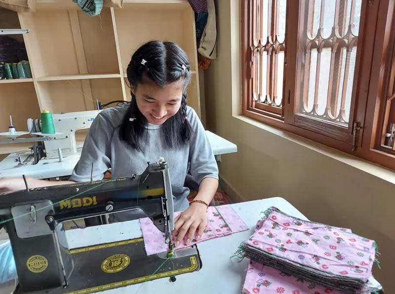 Worker at Beni Handicrafts making reusable menstruation kits, known as Freedom Kits